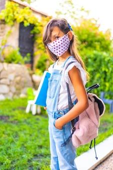 フェイスマスクが学校に戻る準備ができている白人の女の子。新しい正常性、社会的距離、コロナウイルスのパンデミック、covid-19。ジャケット、バックパック、手元のメモ用の青いブロック