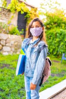 フェイスマスクが学校に戻る準備ができている白人の女の子。新しい正常性、社会的距離、コロナウイルスのパンデミック、covid-19。ジャケット、バックパック、ピンクのドットのマスク、手に青いブロック