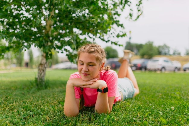 Caucasian girl with freckles and in a pink t-shirt lies on the grass. girl student smiles and enjoys the beautiful summer weather.