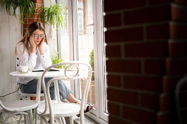 眼鏡をかけた白人の女の子は、カフェのテーブルで働いているときに頭痛や片頭痛があります。フリーランスの朝の仕事と頭の血管れん縮。ビジネスランチとメガネの疲労感。健康の概念。