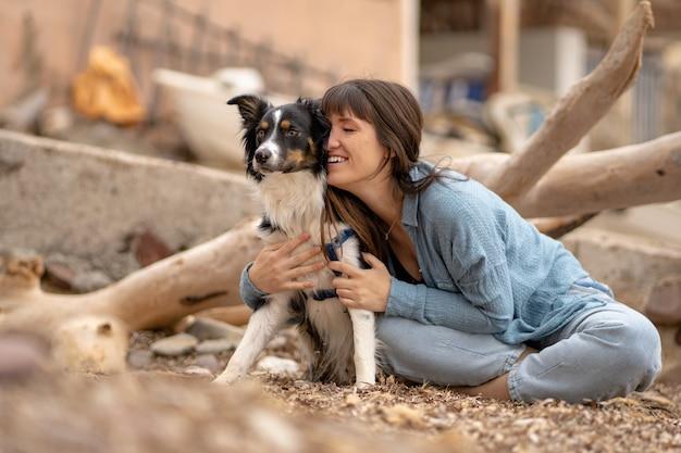 그녀의 보더 콜리 강아지와 함께 해변에서 웃고 있는 백인 소녀