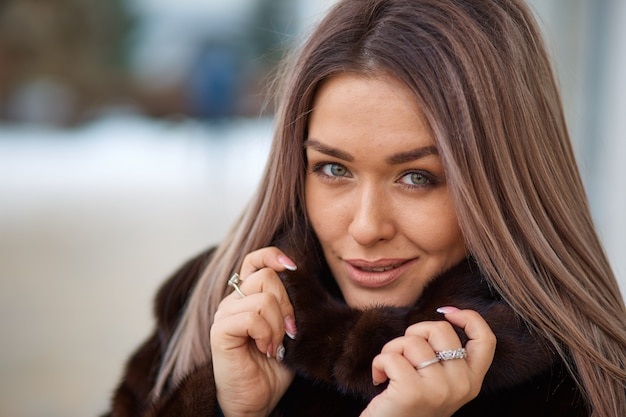 Caucasian girl with long hair big beautiful eyes in winter fur coat in the park
