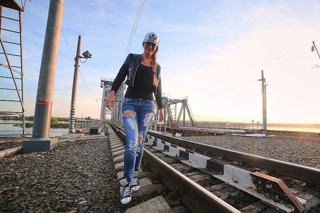 Caucasian girl with long legs in jeans and baseball cap at sunset