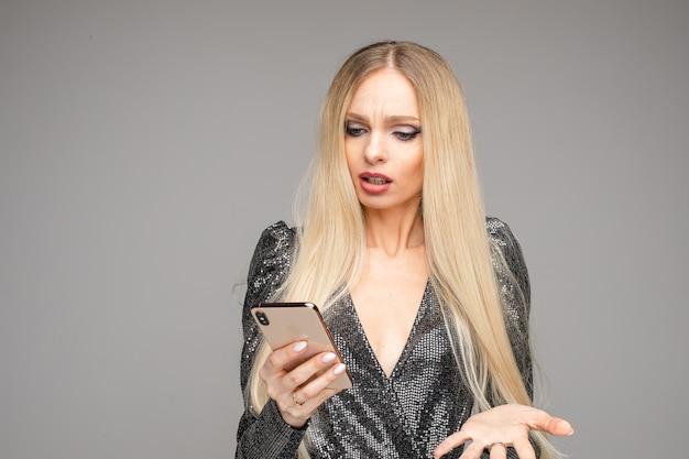 Кавказская девушка с длинными белыми волосами и ярким макияжем держит в руках смартфон, изображение изолировано на сером фоне