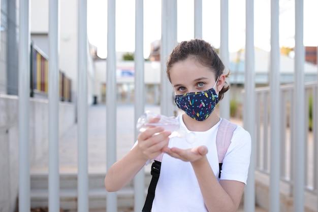 Кавказская девушка с маской наливает водно-спиртовой гель на руки у двери школы в новой нормальной