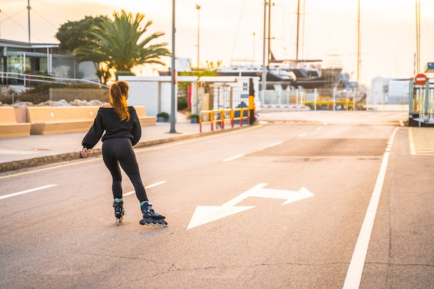日没時にローラースケートでマスクスケートをしている白人の女の子