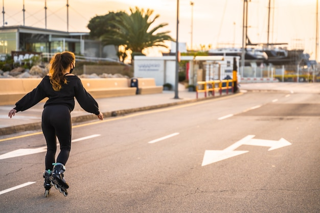 Caucasian girl with mask skating on roller skates at sunset