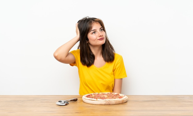 Caucasian girl with a pizza having doubts and with confuse face expression