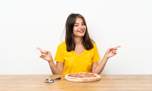 Caucasian girl with a pizza pointing to the laterals having doubts