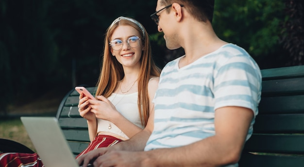Caucasian girl with red hair and freckles wearing eyeglasses is cheering with her lover outside in the park using a laptop on the bench