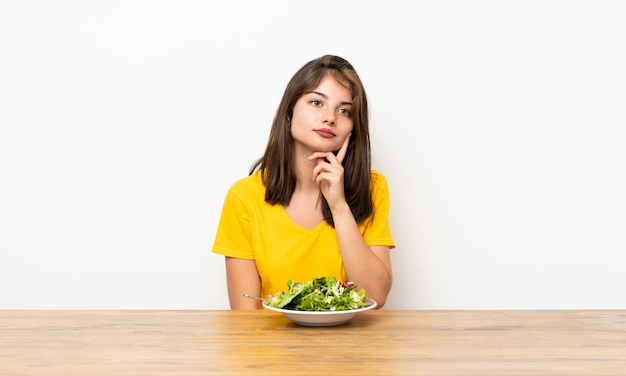 Caucasian girl with salad thinking an idea