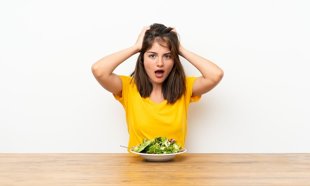 Caucasian girl with salad with surprise facial expression