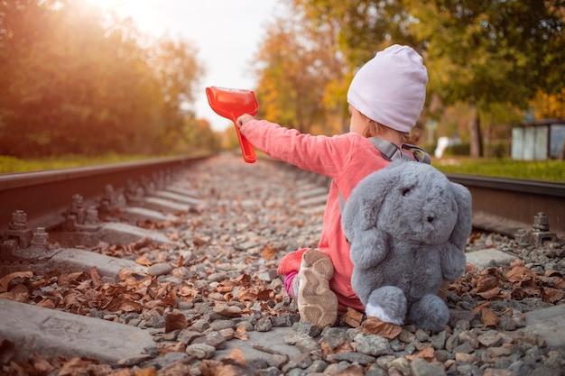 화창한 가을 날 철도 트랙에 장난감을 가진 백인 소녀