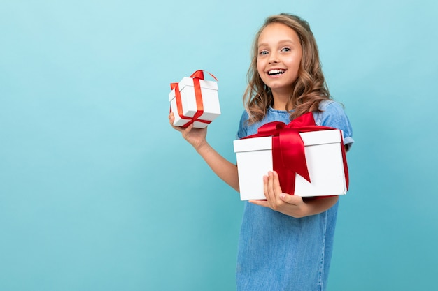 Caucasian girl with wavy brown hair in blue dress, big hat holds a boxes with gifts and rejoices