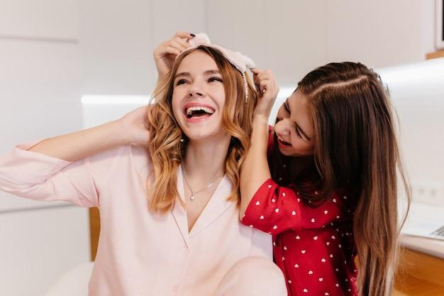 Кавказская рада девушка в розовой маске для глаз смеется, позирует на кухне. фотография в помещении, на которой симпатичные сестры шутят по утрам.