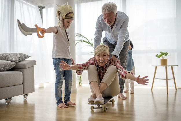 Caucasian grandfather pushing grandmother  on skateboard inside with grandson wearing pirate costume