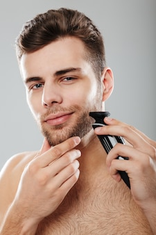 Caucasian guy 30s being undressed at home touching his chin and shaving face with trimmer over grey wall