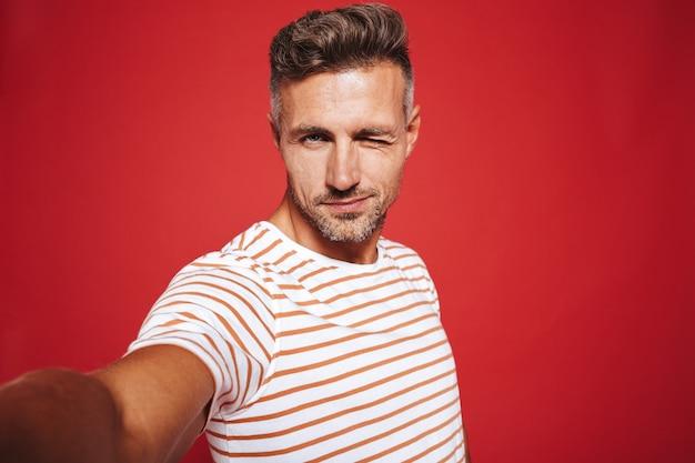 Кавказский парень 30-х в полосатой футболке улыбается, делая селфи на красном фоне