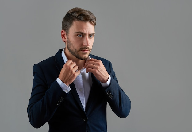Кавказский парень деловой костюм на сером