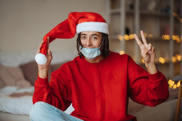 Caucasian guy in face mask and santa claus hat
