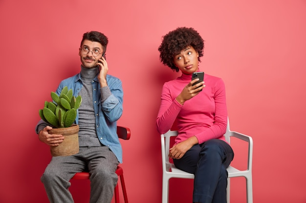 Caucasian guy has telephone talk holds pot of cactus and poses at home on chair. bored dark skinned woman holds cellular and thinks what answer to give. people and modern technologies