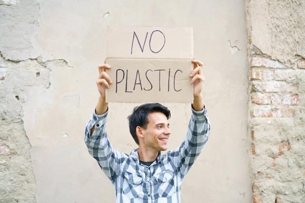 쓰레기 오염으로부터 플라스틱 환경 보호 개념이 없는 비문을 들고 있는 백인 남자