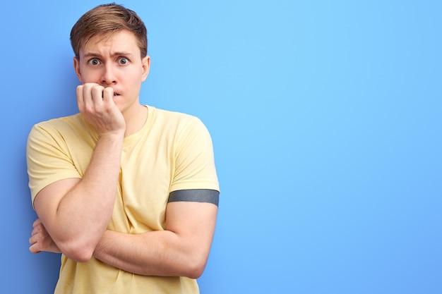 白人の男は、爪を噛む口に手を当ててストレスと緊張を感じています。不安障害。孤立した青い背景