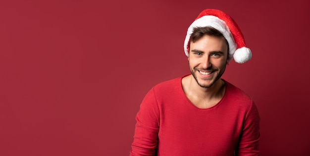 Caucasian guy in red sweater and santa hats