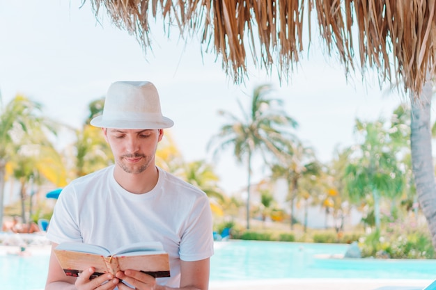 Caucasian guy relaxing near pool with amazing view and reading book