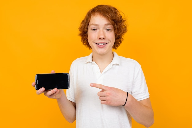 Caucasian guy in a white shirt with a smartphone with a blank template on a yellow background with copy space.