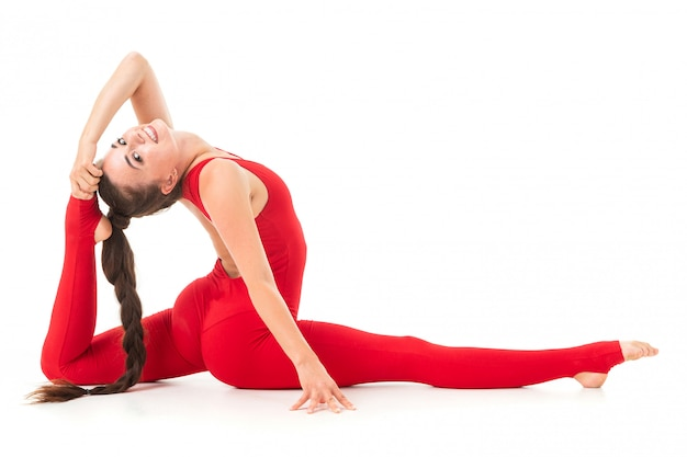 Caucasian gymnast with athletic body sits on a floor and does warm-up and stretch muscles and relax
