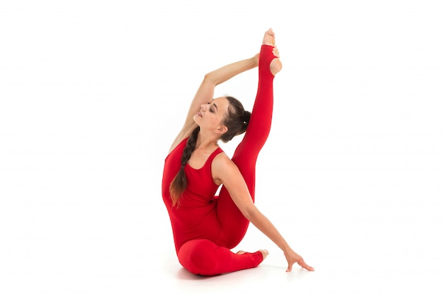 Caucasian gymnast with athletic body sits on a floor and does warm-up and stretch muscles