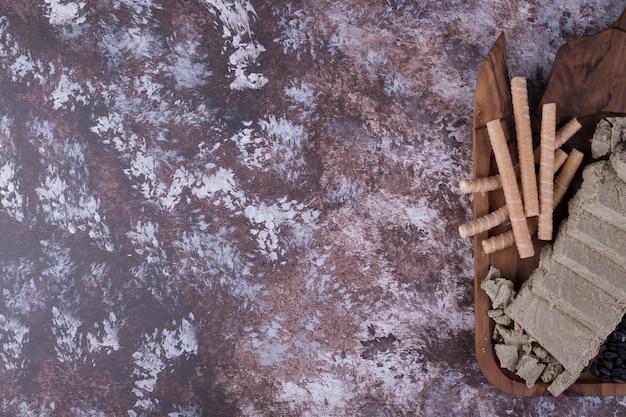 白人のハルヴァをスライスし、木製の大皿にワッフルスティックを添えて