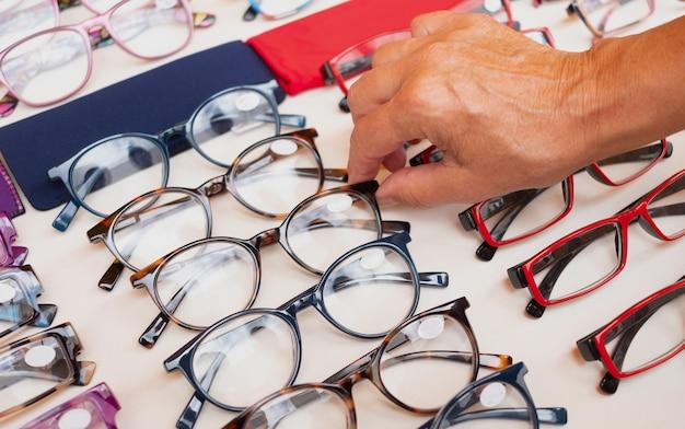 色でいっぱいの眼鏡を選ぶ女性の白人の手。市場にいる1人の高齢者。豊富な品揃え