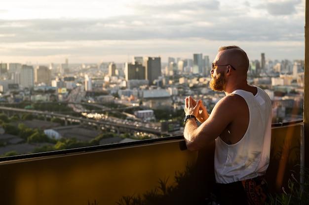 Кавказский красавец бородатый брутальный мужчина наслаждается закатом и видом на город бангкок с высокого этажа