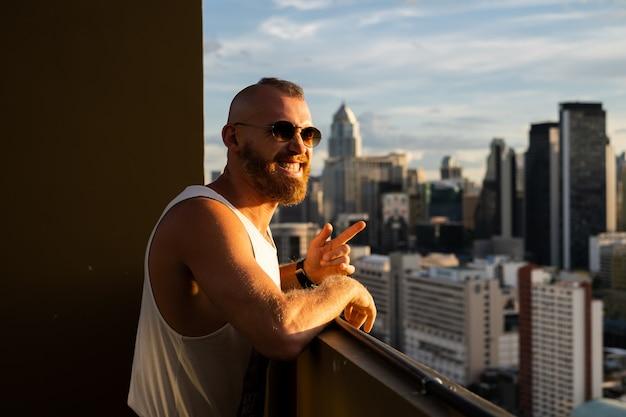 高層階からバンコクの街の夕日と景色を楽しむ白人ハンサムなひげを生やした残忍な男