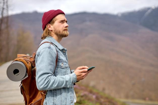 Кавказский красавец брутальный бородатый мужчина путешествует по дикой природе с помощью смартфона