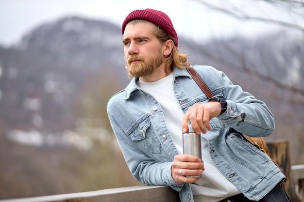 보온병으로 야생의 자연을 여행하는 백인 잘생긴 잔인한 수염 난 남자