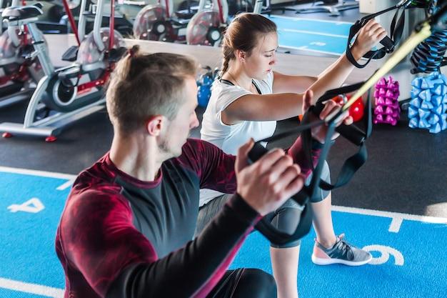 Кавказский красивый мужчина и молодая женщина присоединяются к уроку trx спортивного клуба, тренирующемуся в тренажерном зале. молодая мускулистая пара сосредоточена, делая упражнения на сопротивление всего тела в помещении. горизонтальное фото