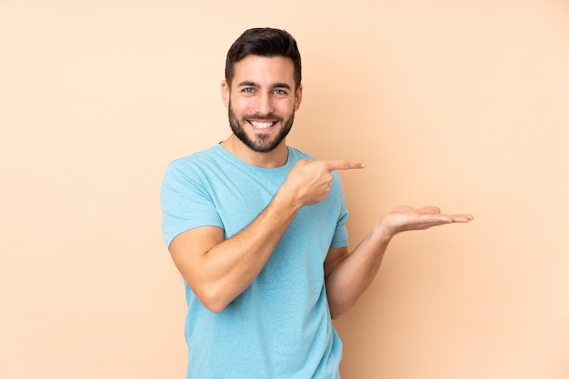 Caucasian handsome man on beige holding copyspace imaginary on the palm to insert an ad