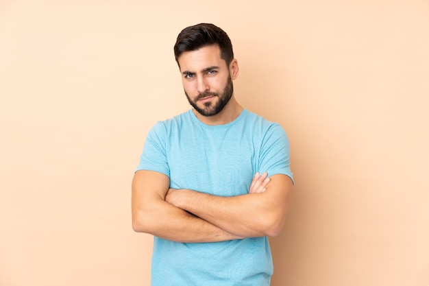 Caucasian handsome man on beige wall feeling upset