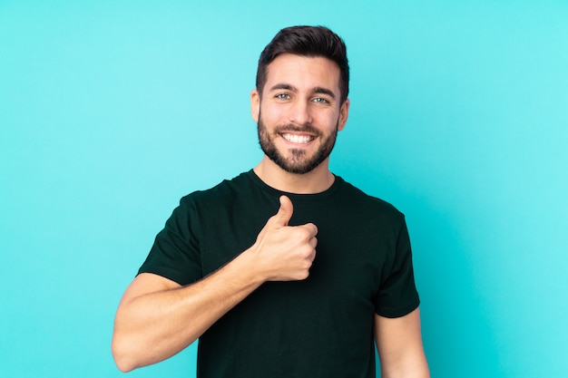 Caucasian handsome man on blue wall giving a thumbs up gesture