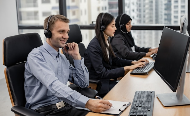 Caucasian handsome man and group of diverse telemarketing customer service staff team in call center. call center worker accompanied by team. smiling of customer support operator at work.