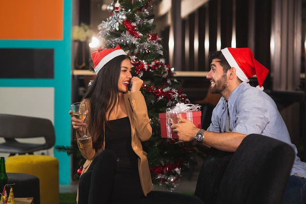 Кавказский красавец держит подарочную коробку, чтобы удивить азиатскую подругу празднует рождество