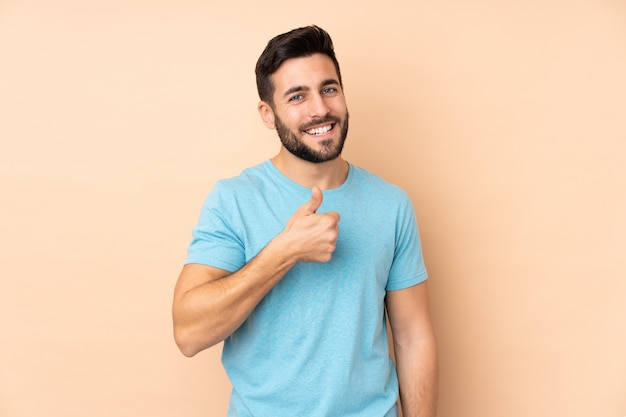 Caucasian handsome man isolated on beige wall giving a thumbs up gesture