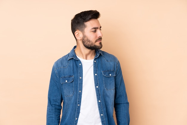 Caucasian handsome man isolated on beige wall looking to the side