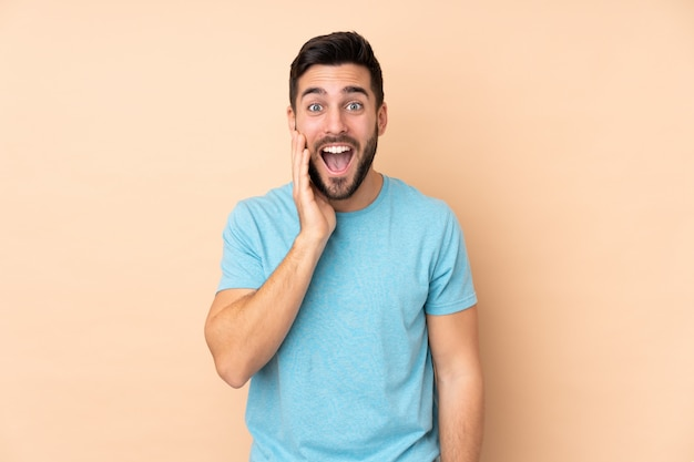 Caucasian handsome man isolated on beige wall with surprise and shocked facial expression