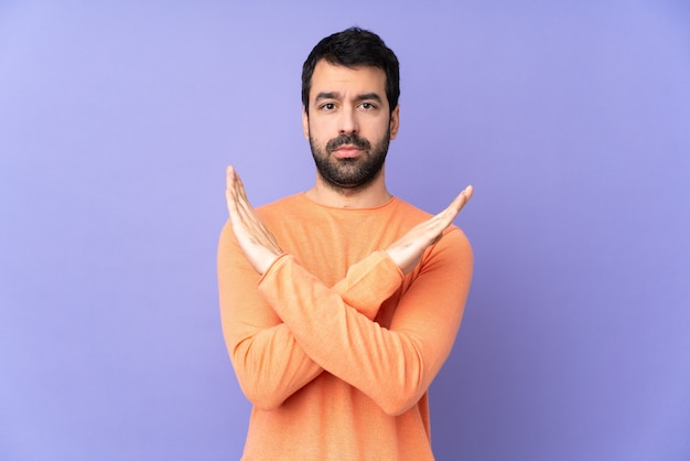 Caucasian handsome man over isolated purple making no gesture