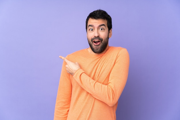 Caucasian handsome man over isolated purple wall surprised and pointing side