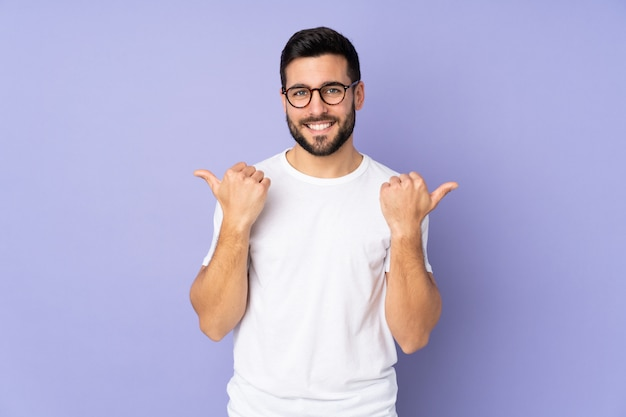 Caucasian handsome man over isolated wall with thumbs up gesture and smiling